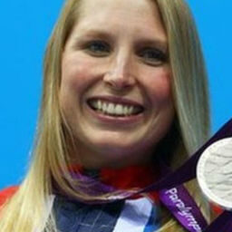 A picture of a women holding a silver medal smiling, the women is called stephanie